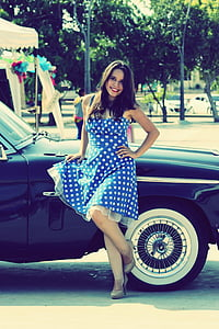 woman in blue and white polka-dot sleeveless dress leaning on black car