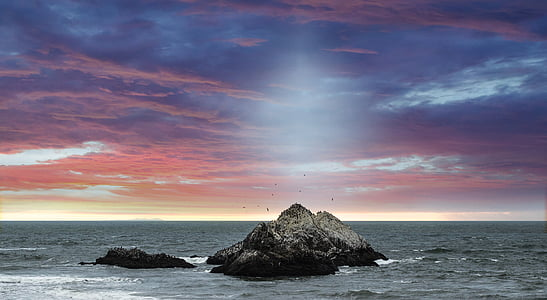 grey stones on sea under blue and red sky