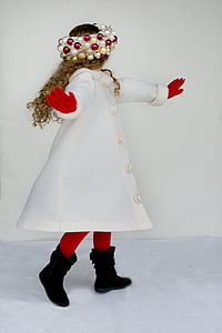 girl wearing white coat standing near white wall