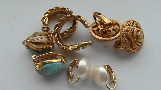 gold-colored jewelries on top of white surface