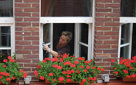 woman cleaning clear glass window
