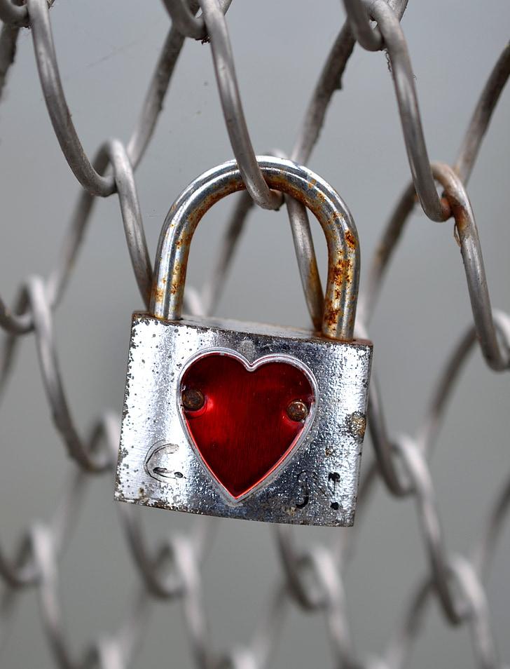 silver padlock in diagonal fence