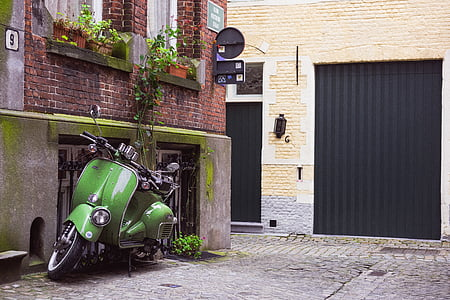 green motor scooter on alleyway