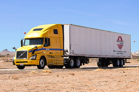 white and yellow tractor unit on road