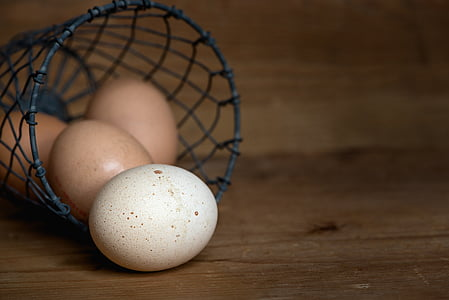 white and brown eggs in black wire basket