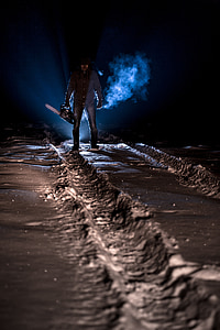 man holding chainsaw during night