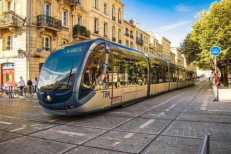 silver electric train in the middle of the street during daytime