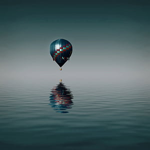 hot air balloon flying over body of water