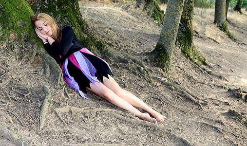 woman in red and purple dress lying on tree roots
