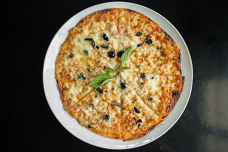 cheesy pizza on round white plate