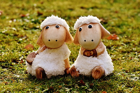 two white sheep decors on green grass