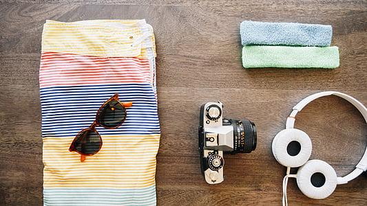 flat lay photography of camera, headphones, sunglasses, and board shorts