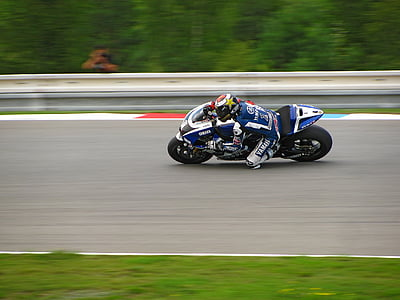photo of man riding on a sports bike during race
