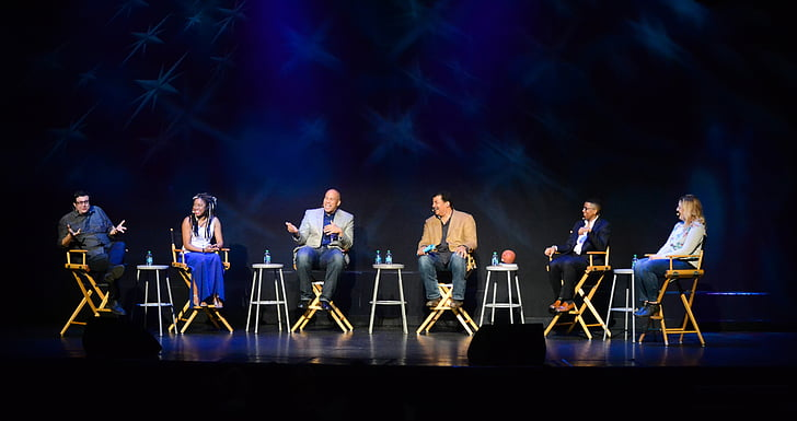 Six People Sitting On Chairs On Stage