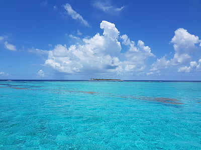 blue ocean water under white and blue cloudy sky