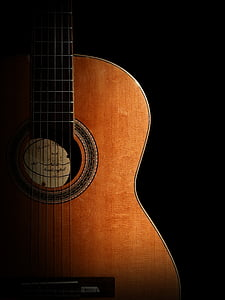 photography of brown classical guitar in dark background
