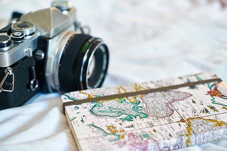 map notebook beside silver bridge camera