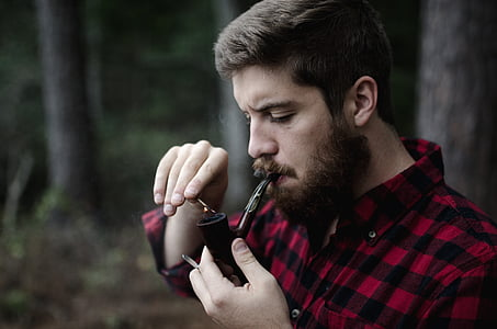 man in black and red gingham dress shirt holding smoking pipe