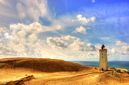 gray lighthouse on brown sand during blue cloudy day