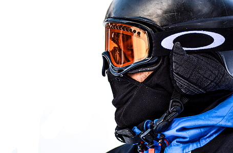 person wearing orange Oakley snow goggles with black frame