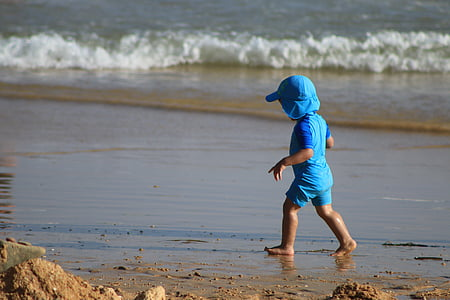 toddler wearing blue shirt walking on shore near sea