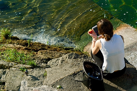 woman using smartphone beside body of water