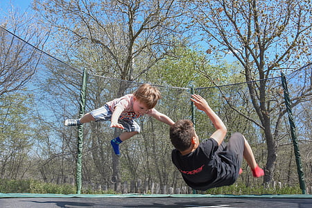 two children playing on a trampoline