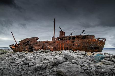 brown ship wreck on rocky shore