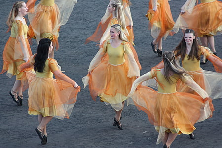 group of women wearing yellow and orange dresses dancing together