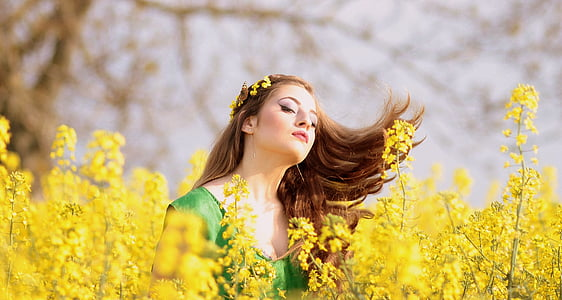 selective focus photography of woman wearing headpiece in field of yellow petaled flower