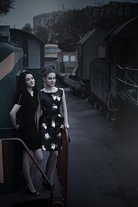 two woman standing on sidewalk