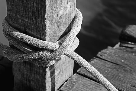 grayscale photo of tied rope on lumber