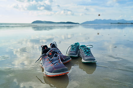 two pairs of athletic shoes on grey sand beach shore
