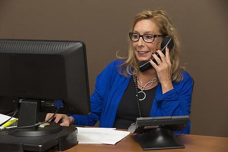 woman in blue cardigan taking phone calls