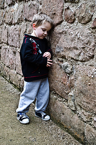 boy leaning on brown concrete wall