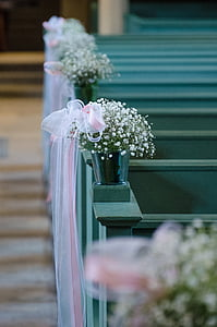 white baby's breath flowers in gray pot on top gray wooden pew