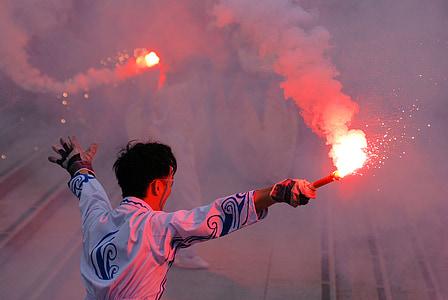 man waving flare sticks