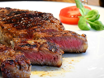 roasted steak with sliced tomato on white plate