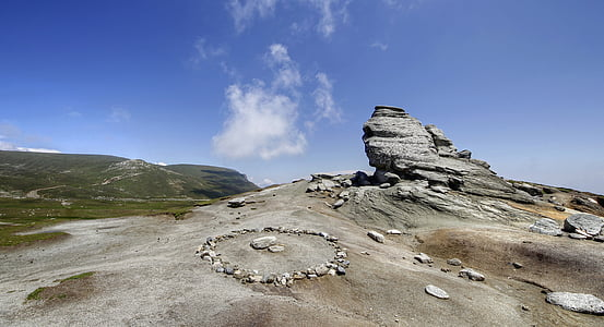 round gray stone formation under white clouds and blue skies at daytime