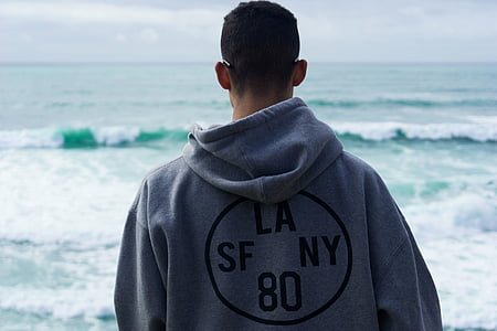 man wearing gray LA SF NY 80 hooded jacket standing near sea during daytime