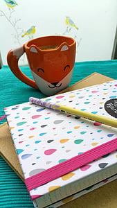 orange and white fox mug near notebook