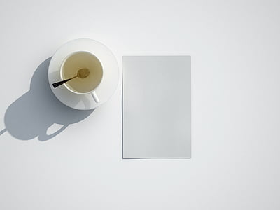 white cup on top of saucer near paper
