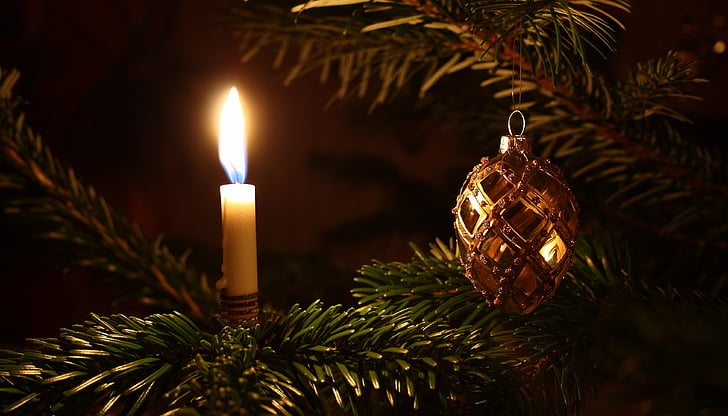 lighted taper candle beside Christmas ornament hanging on fir tree