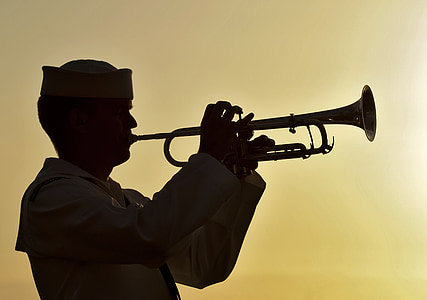 silhouette of man playing wind instrument