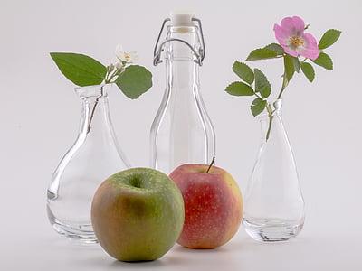 two apple fruits beside three glass bottles