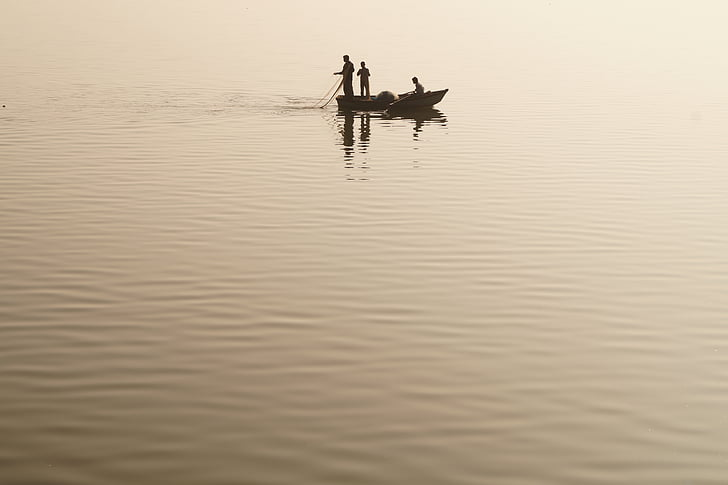 three men on the boat in the middle of the lake