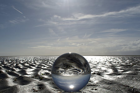 round clear glass ball on sand