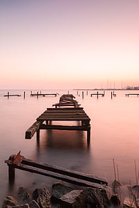 broken dock pier in body of water