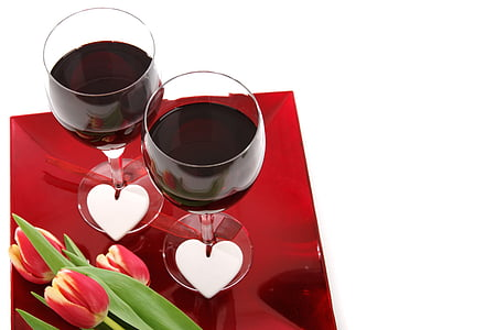 two wine glass with red wine inside beside tulip flowers