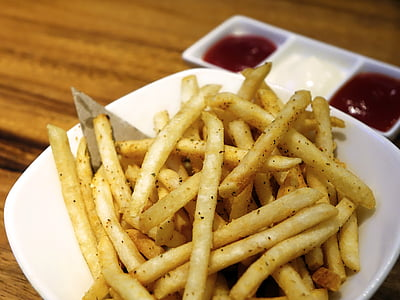 fries with sauce on bowl placed on wood plank